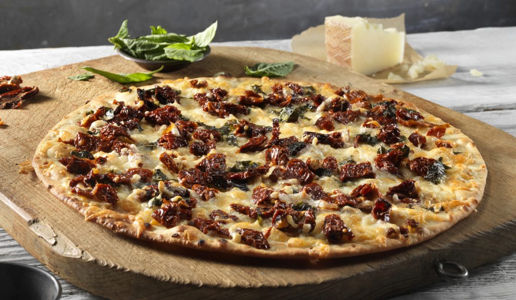 Basil and sun-dried tomato pizza with cheese, on top a Stonefire thin crust pizza.